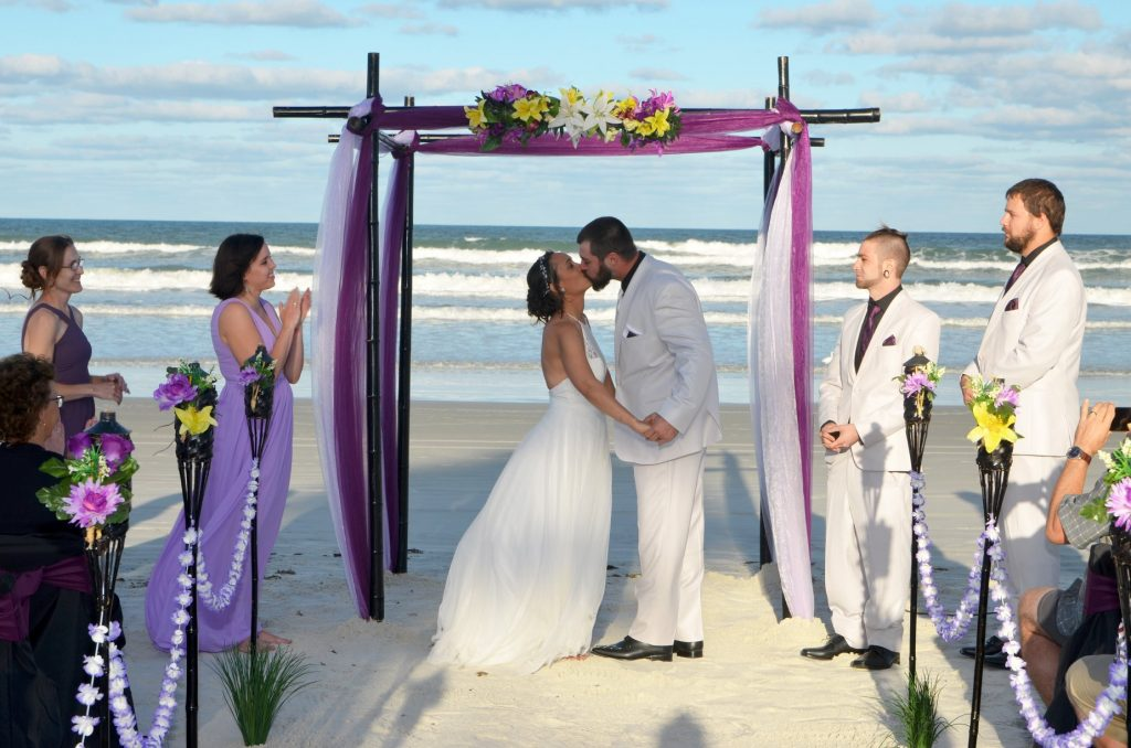 Purple fabric on black bamboo wedding arch with couple kissing on Daytona Beach