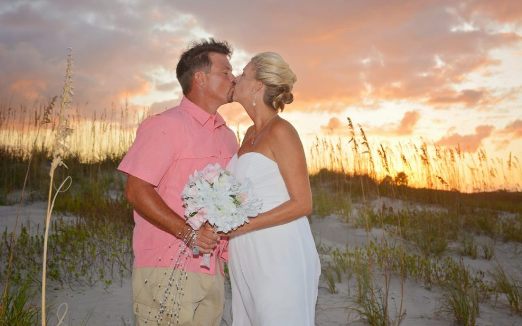 Couple kissing at sunset after beach wedding Florida