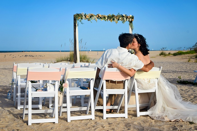Wedding couple kissing on white chairs in St. Augustine