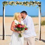 Couple kissing under beach wedding arch St. Augustine FL