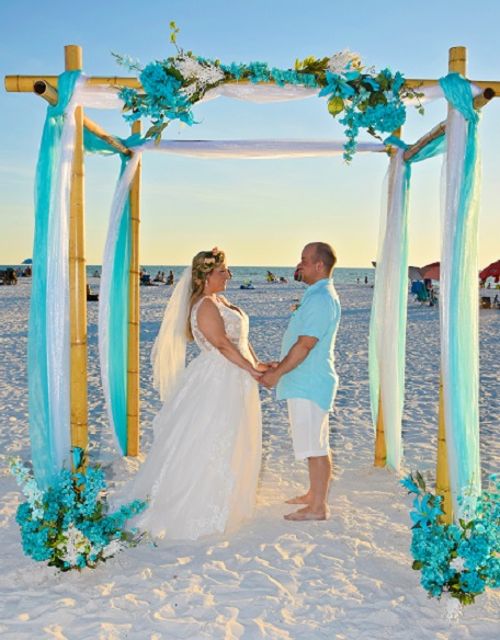 Teal decorations at Clearwater beach wedding with couple holding hands