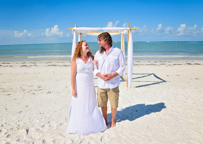 Wedding couple walking on Fort Myers Beach after ceremony