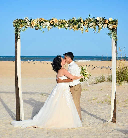 Bride and Groom in St. Augustine kiss at beach wedding under rustic floral wedding arch