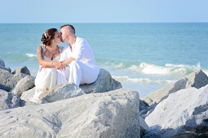 Couple kisses on rocks after wedding on St. Augustine Beach, FL
