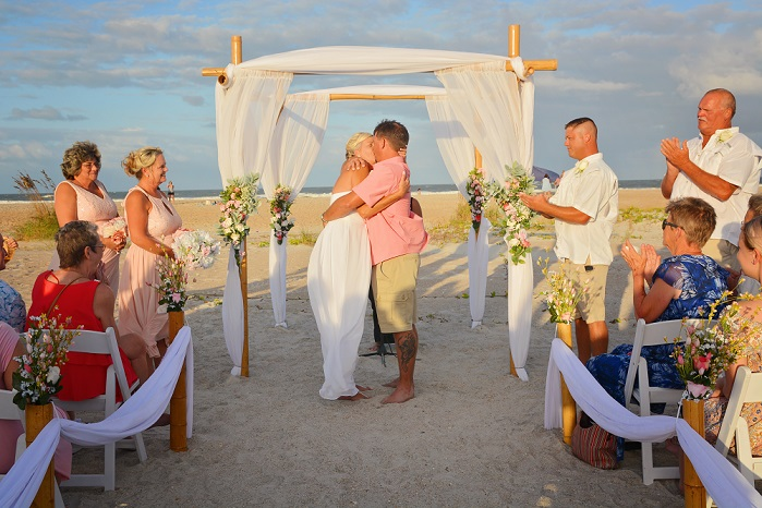 Couple just married kissing on the beach holding a sign