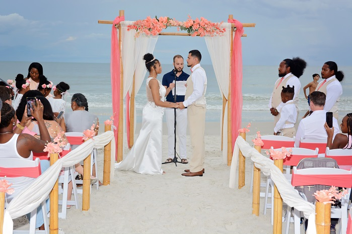 Bride and groom with coral wedding decor on the beach
