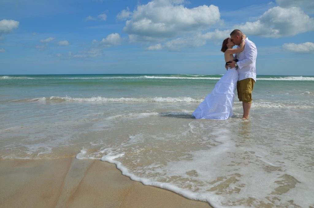 Couple embraces in the sea after wedding on Daytona Beach.