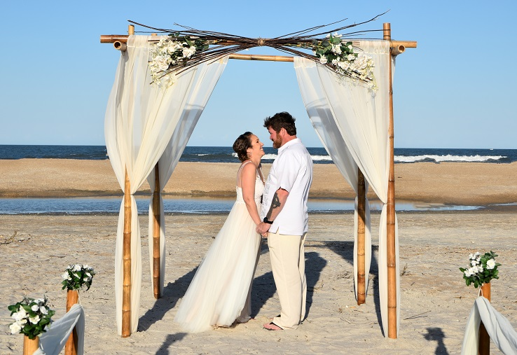 Natural branches and flowers on wedding arch Daytona Beach with couple saying vows