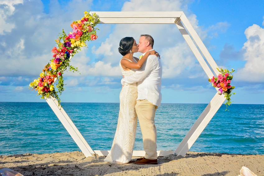 Couple kisses under white geo wedding arch on Atlantic Florida beach