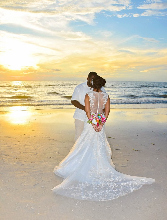 Wedding couple kissing on Clearwater Beach at sunset vow renewal