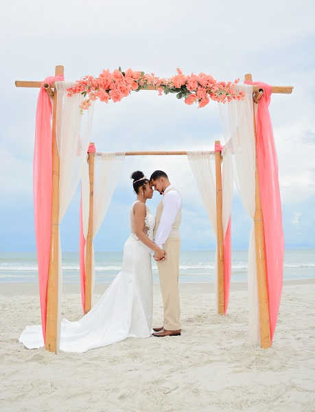 Bride and groom say vows under wedding canopy on the beach