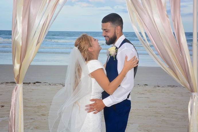Couple gazes at each other under wedding arch on Daytona Beach