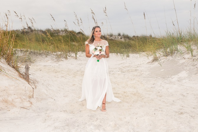 Bride walks between sand dunes at beach wedding in Destin FL