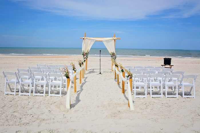 Bamboo wedding arch with flowers and white chairs on Daytona Beach
