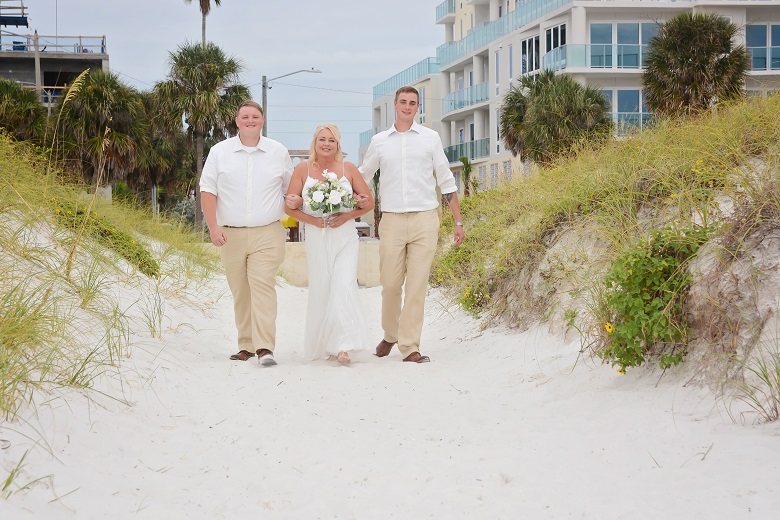 Clearwater beach bride walks towards groom with two sons