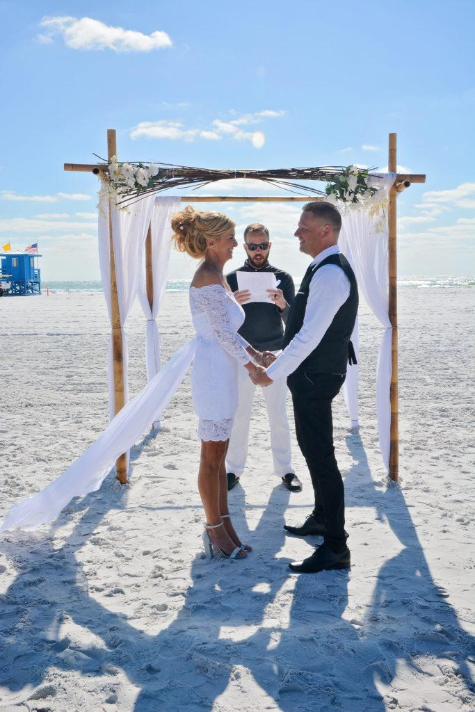 Couple holds hands during Siesta Key wedding