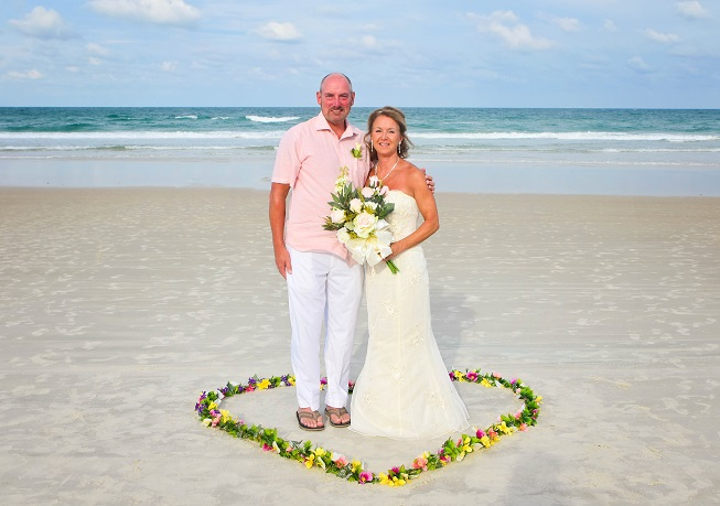 Eloping couple stands in petal hearts on Daytona Beach, FL