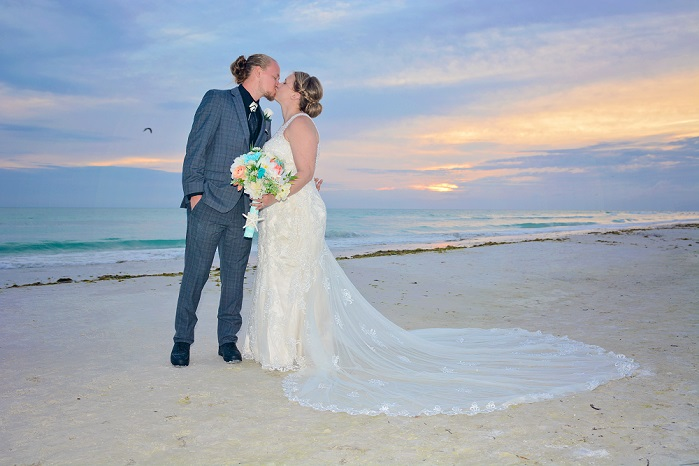 Sunset behind wedding couple kissing on a Gulf beach in FL