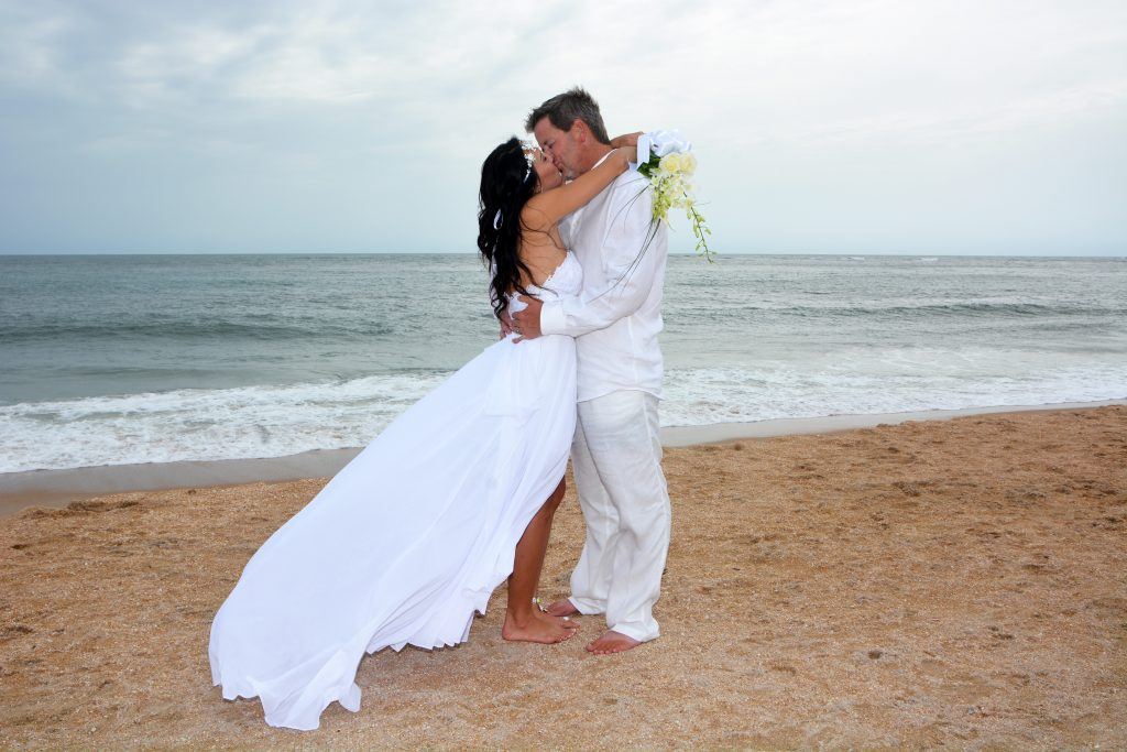 Couple kisses on St. Augustine shoreline after beach wedding ceremony