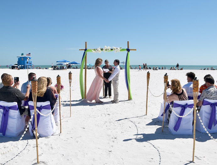 Couple saying vows under lime and bamboo wedding arch on Siesta Key Beach, FL