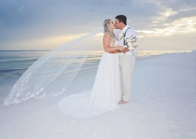 Bride with veil kissing groom on Siesta Key Beach