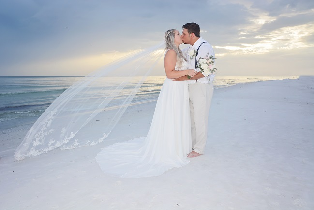 Bride with veil kissing groom on Siesta Key Beach