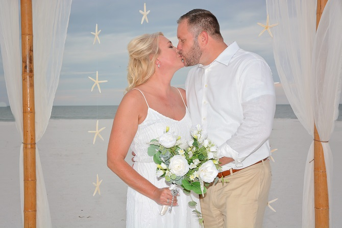 Couple kisses after saying I do on Clearwater Beach under bamboo canopy with starfish hanging