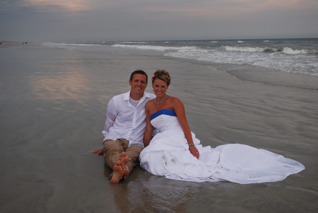 Tanned wedding couple in Atlantic surf at night