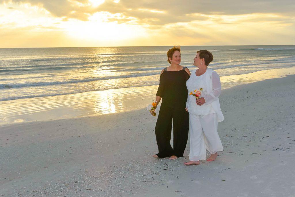Same sex couple walks on Siesta Key beach at sunset after wedding