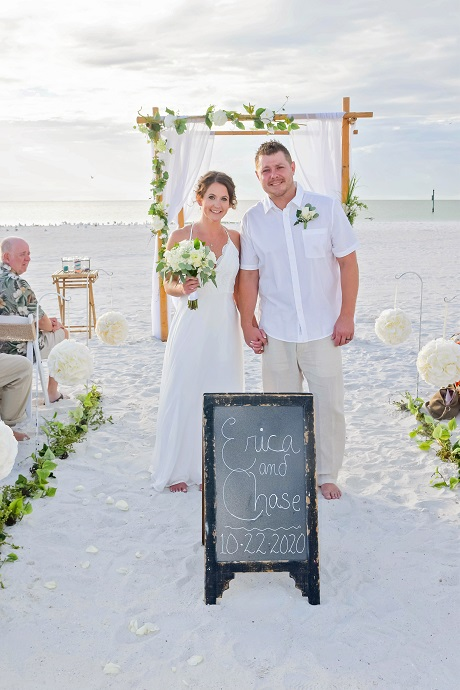 Clearwater couple poses by chalkboard sign announcing marriage on beach