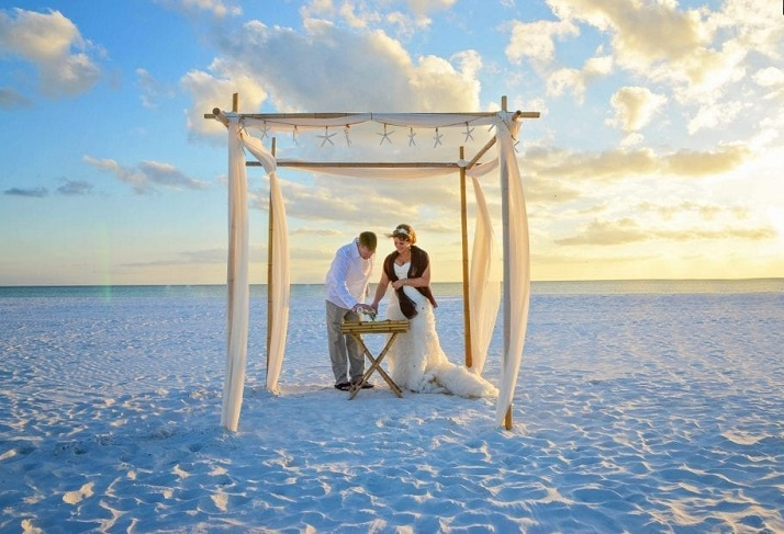 Pass-A-Grille Beach couple at sunset under wedding canopy