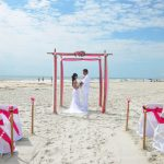 Pink wedding arch and couple on St. Augustine Beach
