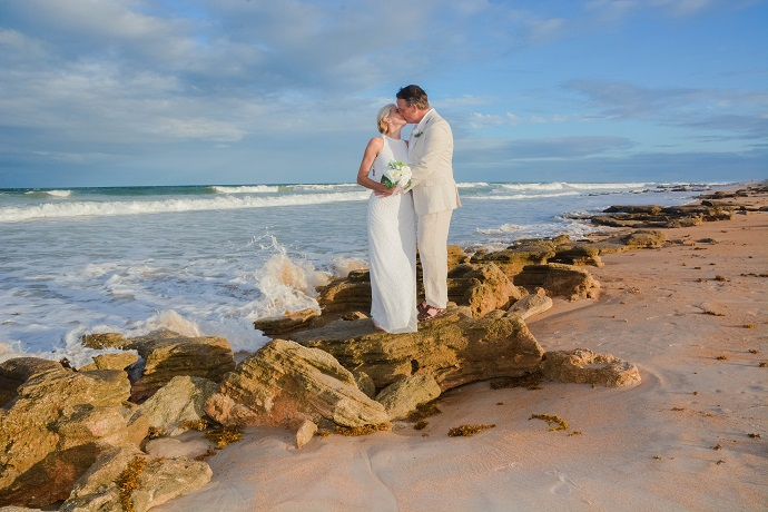 Couple embraces on rocks on St. Augustine Beach after wedding