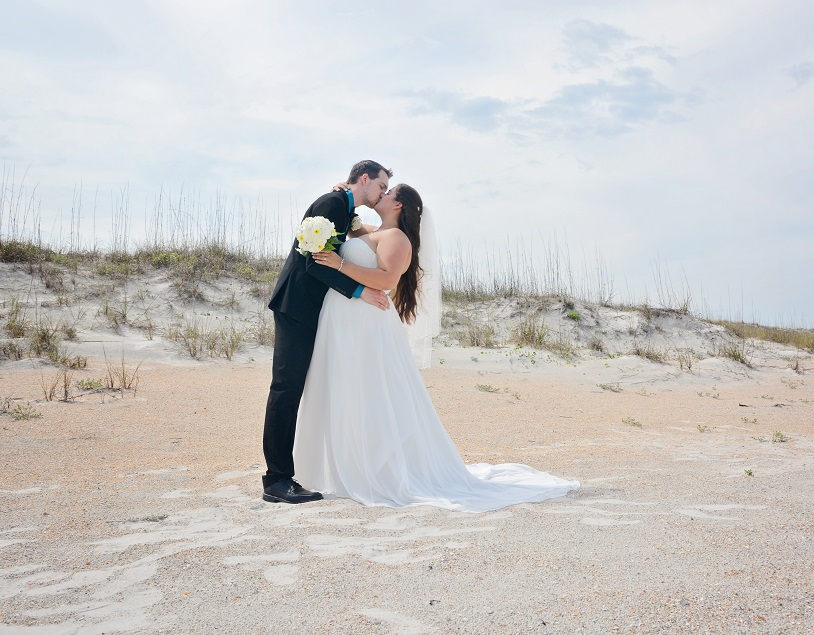 Bride and Groom kiss by dunes in St. Augustine Beach, FL