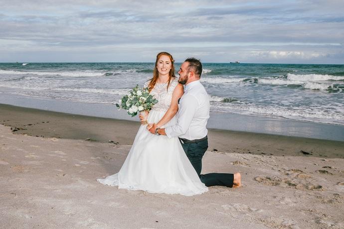 Cocoa Beach Wedding couple kneeling on Beach by ocean