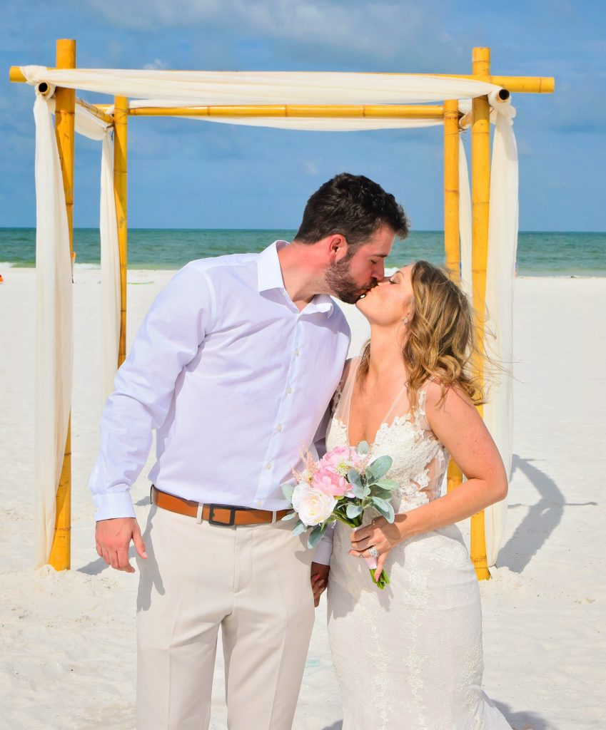 Couple kisses under bamboo wedding arch on Clearwater Beach