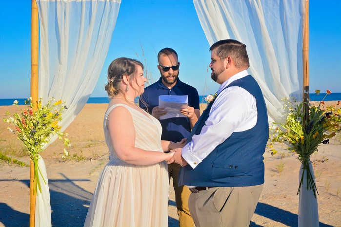 Couple says vows under rustic floral wedding arch on Florida beach