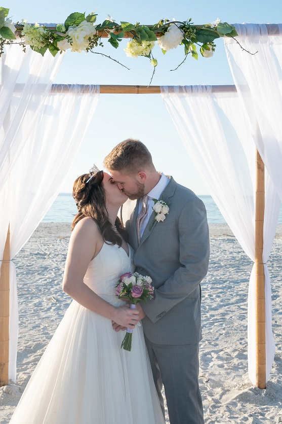 Sand Key Couple kissing under floral wedding arch on Sand Key Beach