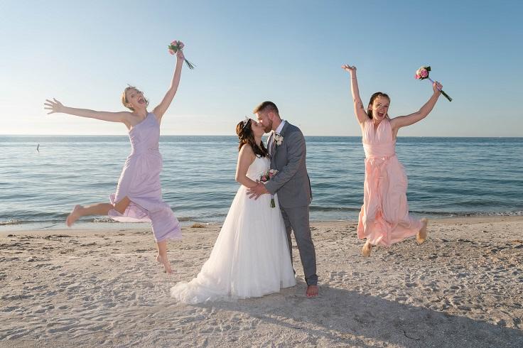 Bridesmaids jumping in Sand Key at beach wedding