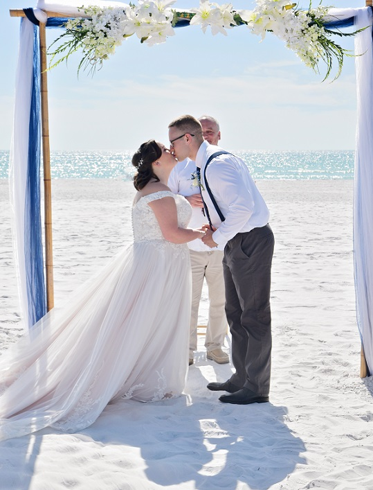Couple kisses on Siesta Key under wedding arch