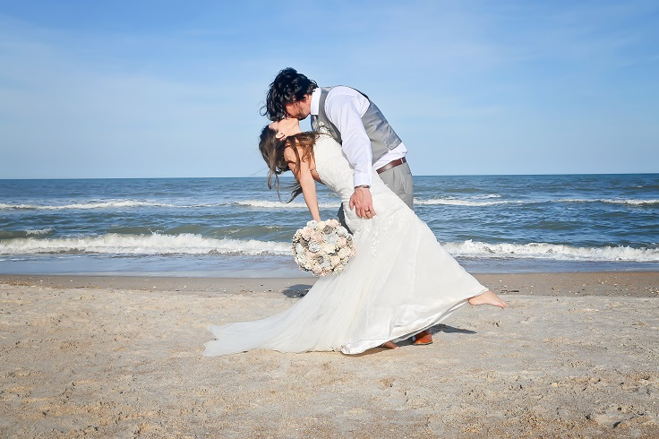 Bride and groom kissing by ocean