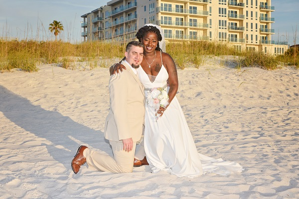 Clearwater Couple just married at beach wedding poses on sand by hotel
