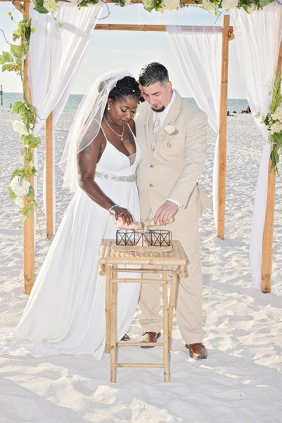Clearwater couple pours sand into unity container on beach