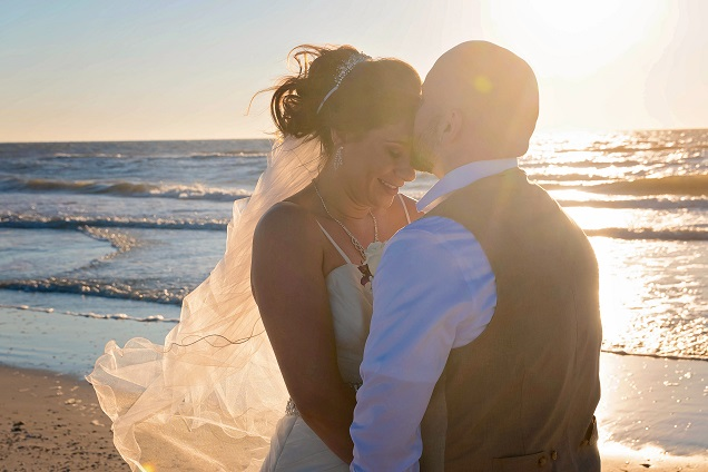 Couple kissing by Gulf water in Clearwater Beach after wedding