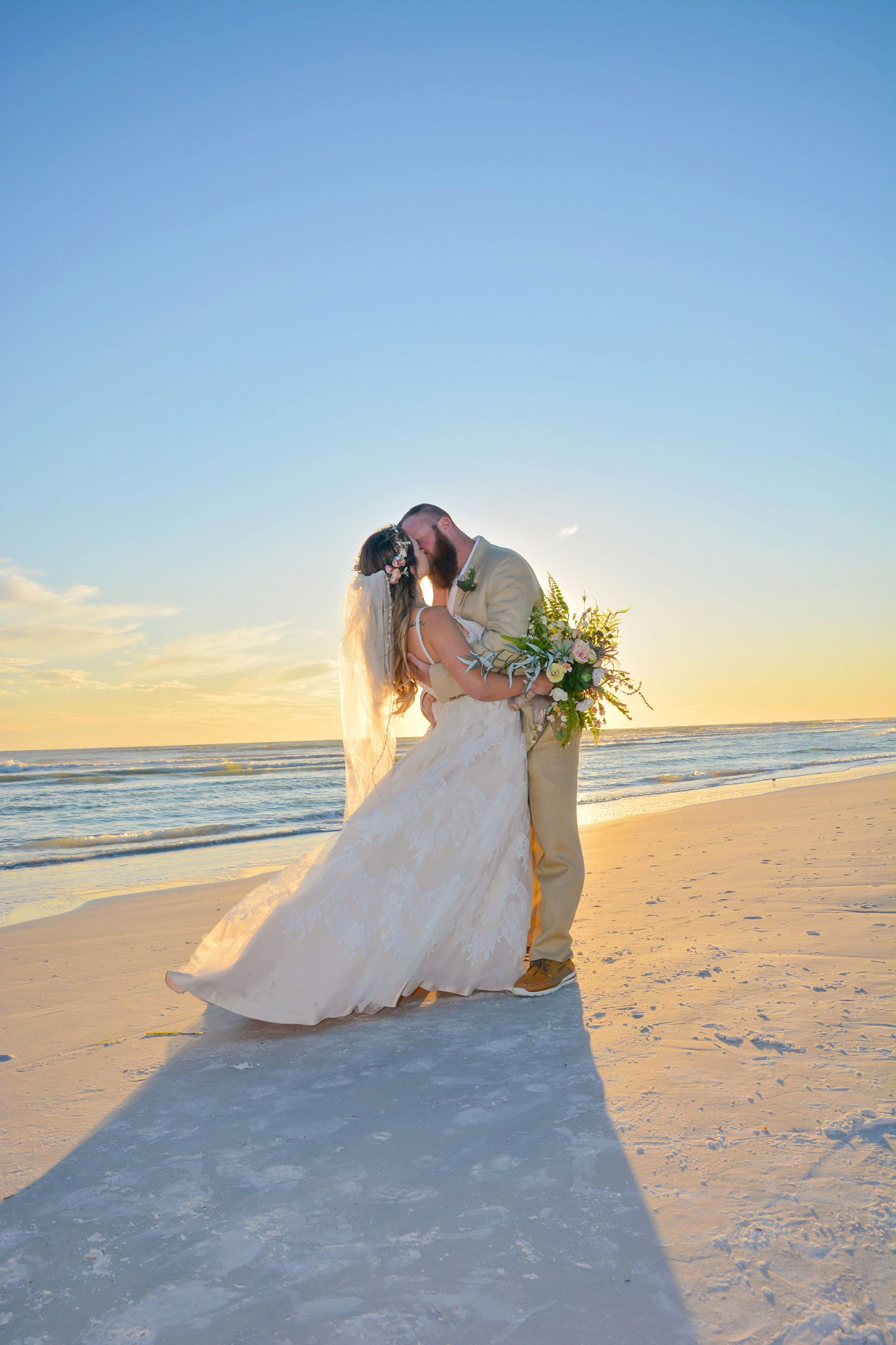 Couple on the beach at the altar holding hands and dancing