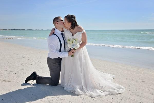 Bride sits on grooms knee on Siesta Key beach