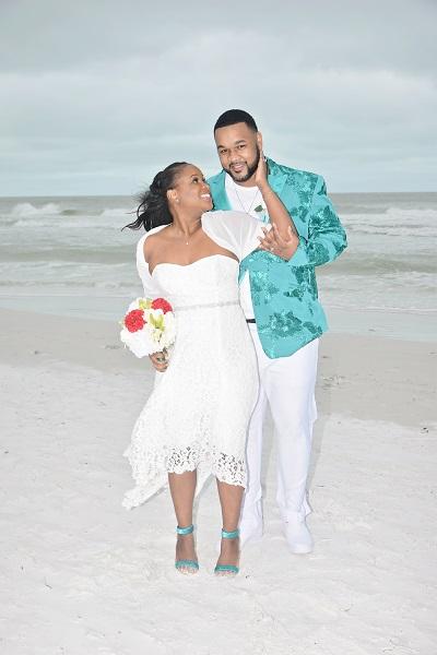 Tea length lace wedding gown on bride beside groom on Florida Gulf Beach