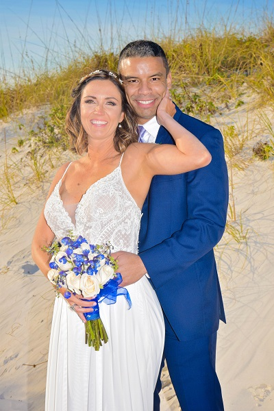 Bride in spaghetti strap lace wedding gown with groom on Gulf beach in Florida
