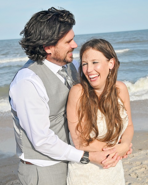 wedding couple laughs by the ocean