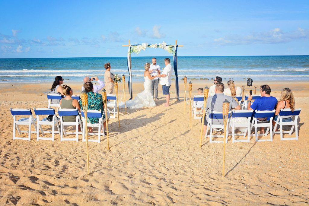 Blue material and flowers on beach wedding arch